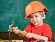 锤击钉子的滑稽的男孩 尝试新的技巧的孩子 单独学习的概念 免版税图库摄影