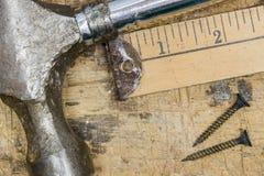 锤子、围场棍子和生锈的螺丝特写镜头在工作凳 免版税图库摄影