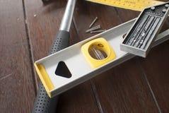 锤子、水平、t方形的统治者和钉子在木材背景 免版税库存照片