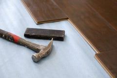 锤子和块与新的层压制品的地板 库存图片