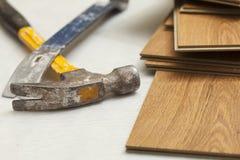 锤子和撬杆与层压制品的地板摘要 库存照片