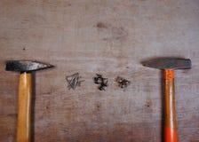 锤子和钉子在木委员会背景 库存图片