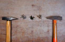 锤子和钉子在木委员会背景 免版税库存图片