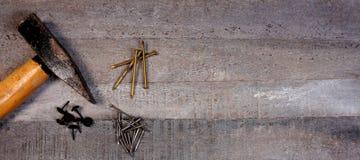 锤子和钉子在自然木背景与拷贝空间您自己的文本的 库存照片