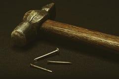 锤子和钉子在黑背景 免版税图库摄影
