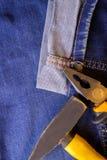 锤子和钳子在蓝色运转的牛仔裤长裤说谎 免版税库存图片