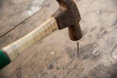 锤子的关闭在木地板上把钉子放 免版税库存图片