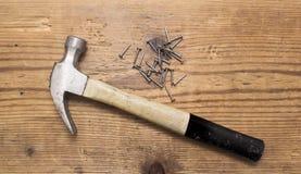 锤子的特写镜头和堆铆钉,在白色背景的钉子 库存照片