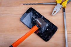 锤子碰撞一个黑智能手机,在它旁边有螺丝刀和钳子 在一个木背景 免版税库存照片