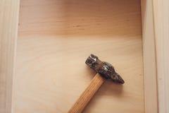 锤子说谎木表面上 说谎工作凳木表面上的葡萄酒锤子  库存照片