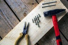 锤子,钉子,稀薄鼻子钳子,在一个木酒吧的螺丝 库存图片