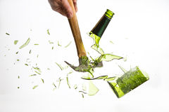 锤击一个绿色玻璃瓶在白色背景隔绝的断裂 免版税图库摄影