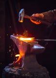 锤击一把高热金属标尺的铁匠 免版税库存照片