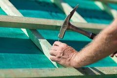 锤击在顶梁的盖屋顶的人一个钉子 免版税库存照片