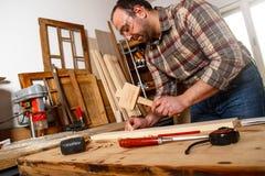 锤击木定缝销钉的木匠 库存图片