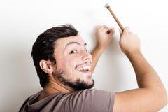 锤击钉子墙壁的年轻人bricolage 免版税图库摄影