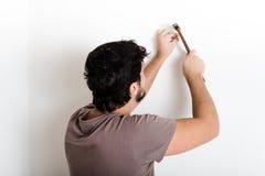 锤击钉子墙壁的年轻人bricolage 免版税库存图片