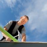 锤击钉子的微笑的盖屋顶的人 免版税图库摄影