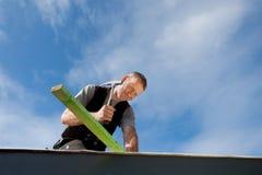 锤击钉子的盖屋顶的人 图库摄影