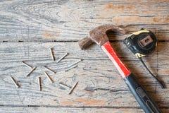 锤击,测量磁带和大头钉在木背景 免版税库存照片
