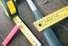 锤击, t正方形、卷尺、铅笔和钉子在木材背景 免版税图库摄影