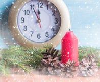 锥体和分支围拢的红色蜡烛与一个时钟在背景中 免版税库存图片