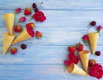 锥体wafflefor冰淇凌,果子樱桃草莓,在木的蓝色的茶点样式创造性的玫瑰色花纹花样 库存图片