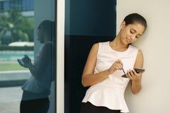 键入与在智能手机的笔的愉快的女商人 库存照片