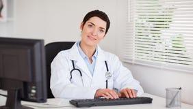 键入与她的计算机的微笑的医生 库存照片