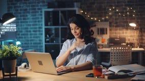 键入与膝上型计算机然后打呵欠的工作的被用尽的少女在办公室在晚上 影视素材
