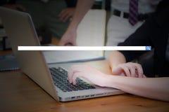 键入使用与空白的查寻酒吧的便携式计算机数字信息的年轻女商人的手 库存图片