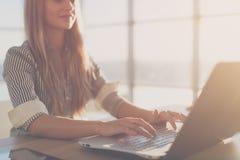 键入使用膝上型计算机键盘的女作家在她的工作场所早晨 妇女网上文字博克,侧视图关闭 免版税库存图片