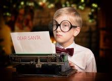 键入信件的男孩对打字机的圣诞老人 免版税库存照片