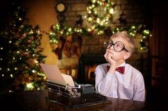键入信件的男孩对打字机的圣诞老人 免版税库存图片