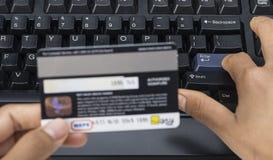 键入和付与信用卡的妇女手的图象网上付款 免版税图库摄影