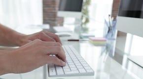 键入在一个个人计算机的键盘的雇员的特写镜头 免版税库存图片