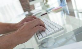 键入在一个个人计算机的键盘的雇员的特写镜头 库存照片