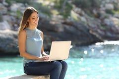 键入在一个热带海滩的一台膝上型计算机的妇女 免版税库存图片