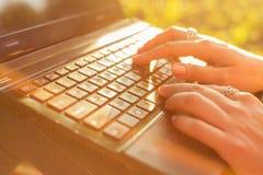 键入在一个膝上型计算机键盘的妇女在一个温暖的晴天户外 库存照片