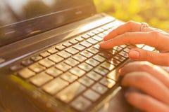 键入在一个膝上型计算机键盘的妇女在一个温暖的晴天户外 免版税库存照片