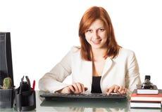 键入在一个计算机键盘的微笑的女孩在办公室 库存图片