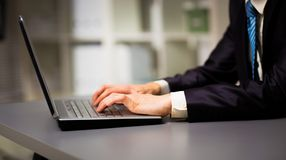 键入在一台现代膝上型计算机的人在办公室 免版税库存照片