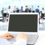 键入在一台现代膝上型计算机的人在办公室 免版税库存图片
