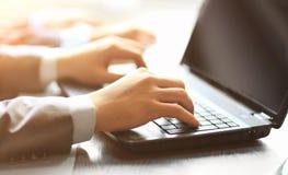 键入在一台现代膝上型计算机的人队在办公室 免版税库存照片
