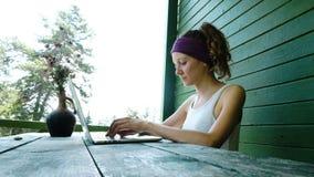 键入在一台膝上型计算机的年轻女商人旅游自由职业者在夏天户外在娱乐中心 股票录像