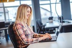 键入在一台膝上型计算机的微笑的妇女在办公室 库存照片
