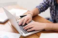 键入在一台膝上型计算机的手在现代办公室,特写镜头 库存照片