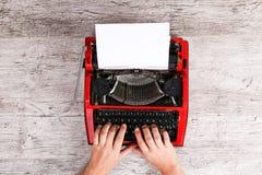 键入在一红色打字机maschine的一个人的手 免版税库存图片