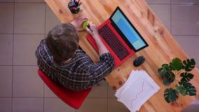 键入在书桌上的膝上型计算机和写关于的年轻白种人商人特写镜头顶面射击一个提示 影视素材