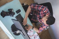 键入在他的计算机上的年轻摄影师在照相讲席会以后 免版税图库摄影